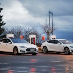 PAIMIO, FINLAND - NOVEMBER 14, 2015: Two white Tesla Model S cars are being charged at Tesla Supercharger station at night. Tesla Supercharging stations charge up to 16 times as fast as public charging stations.